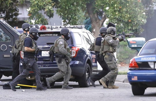 SWAT team members move toward a house on Miller Street in Redding during a standoff that lasted about seven hours before a Redding man was captured.