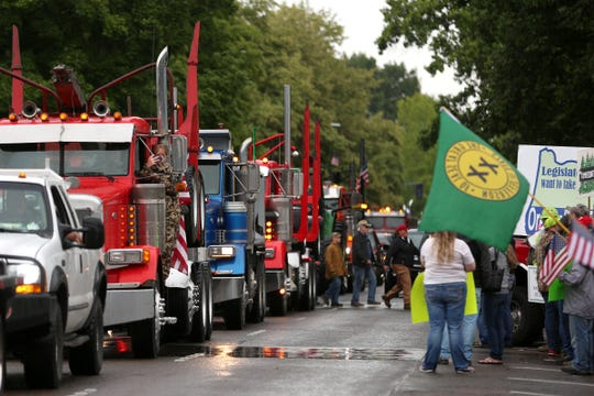 Trucks drive past the Capitol during a rally against HB 2020 at the Oregon State Capitol in Salem on June 27, 2019.