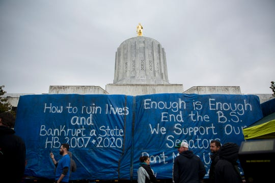 Tarps over a truck bed are written on at a rally against HB 2020 at the Oregon State Capitol in Salem on June 27, 2019.