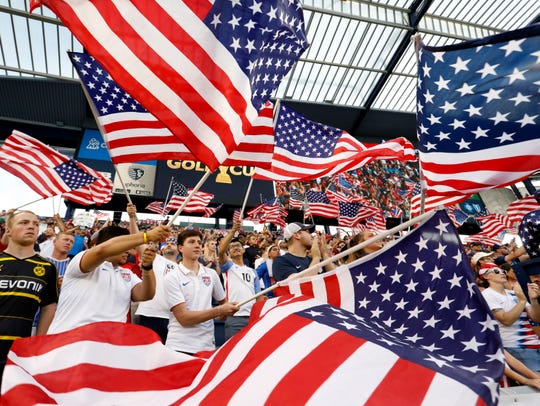 Fans of the U.S. team wave flags as the players are introduced for a CONCACAF Gold Cup soccer match against Panama in Kansas City, Kan., Wednesday, June 26, 2019.