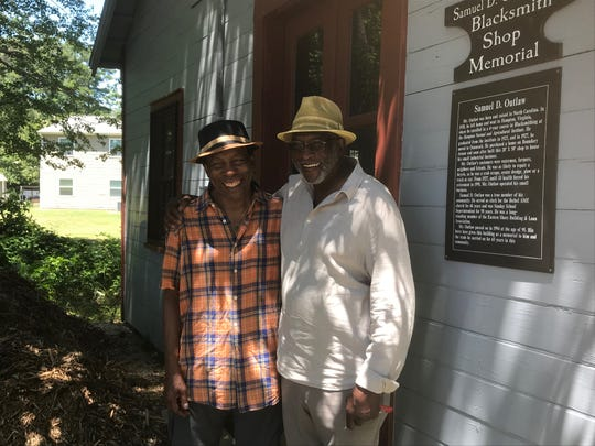 Musician Newman Taylor Baker, left, stands with Gerald Boyd outside the Samuel Outlaw Blacksmith Shop Museum in Onancock, Virginia on Wednesday, June 26, 2019.