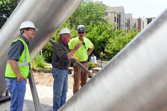 "Artist Dale Lamphere talks to construction workers before giving the ""O.K."" to weld the final half of the Arc of Dreams sculpture in place Thursday, June 27, in Sioux Falls."