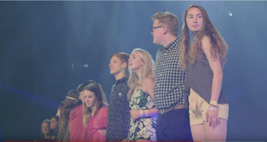 Kickapoo High School students Drew Voris, second from right, and Natalie Gates, in the flowery top, listen on stage as Lady Gaga talks about mental health. The moment was captured in a video by the Born This Way Foundation.