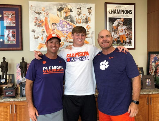 Lincoln senior tight end Sage Ennis takes a photo with Clemson head coach Dabo Swinney and tight ends coach Danny Pearman during a visit in which Ennis committed to play for the Tigers.