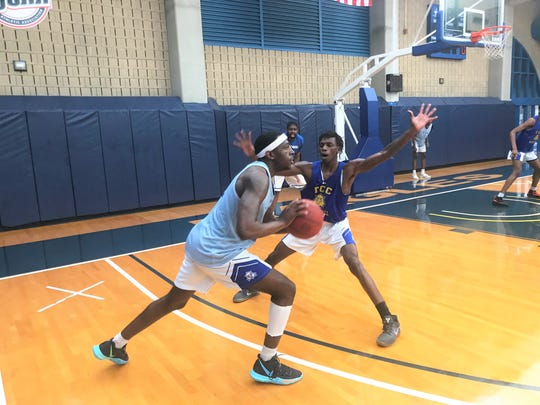 TCC newcomer Tariq Silver, a transfer from Eastern Michigan, looks to make a pass against University of Akron transfer Eric Hester as the Eagles prep for the Summer Showcase.