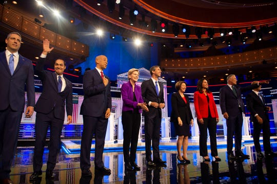 A group of Democratic presidential primary candidates (from left), Rep. Tim Ryan, Sen. Julián Castro, Sen. Cory Booker, Sen. Elizabeth Warren, Rep. Beto O'Rourke, Sen. Amy Klobuchar, Rep. Tulsi Gabbard, Gov. Jay Inslee, and Rep. John Delaney, enter the debate stage Wednesday, June 26, 2019, at the Adrienne Arsht Center for the Performing Arts in Miami.