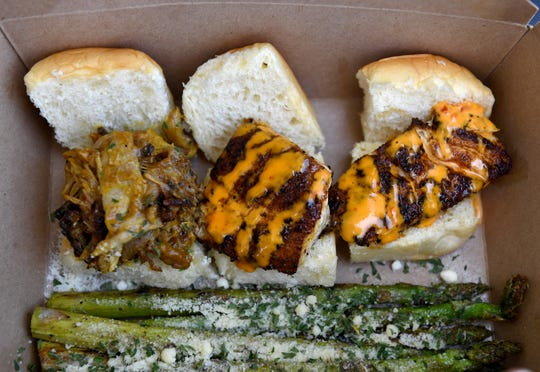 An order of a pulled pork slider (left) and two blackened snapper slider specials are served with a side order of Parmesan grilled asparagus cooked by Tony Weisman in his food truck, Sunset Sliders, while parked along Southeast Dixie Highway at Southeast Hawthorn Street on Thursday, June 27, 2019, in the Golden Gate area, south of Stuart.