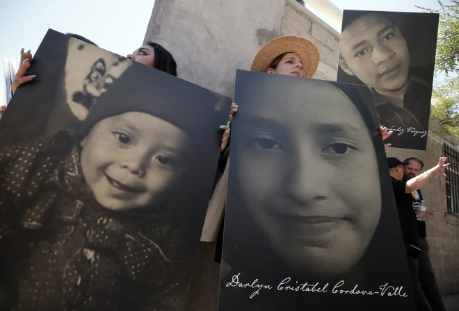 """People traveling across the border into Juarez with Bishop Mark Seitz hold photos of migrant children who have died in U.S. custody as he visits the city to shed light on """"Remain in Mexico"""" or Migrant Protection Protocols."""