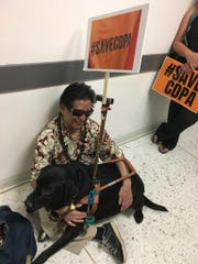 Milton Koja, with his service dog Nash, demonstrates with others from Rockland County-based BRiDGES in support of the Consumer Directed Personal Assistance Program.