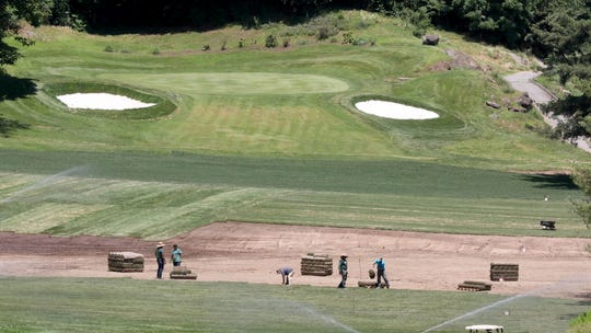 Workers install turf on one of the golf holes at Maple Moor Golf Course in White Plains, June 27, 2019.