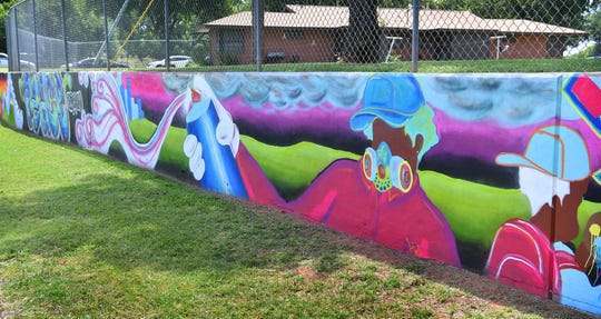 Jacobie Genus designed a mural that stretches 445-feet through a park at Marconi and Harding. Jessica Johnson and Jacob Gardin helped paint the mural, the longest in Wichita Falls.