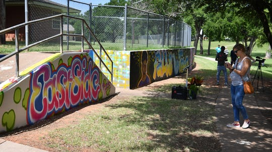 Becky Raeke, a supporter of the arts in Wichita Falls, photographs a small portion of the longest local mural, Jacobie's Wall, a 445-foot artwork designed by Jacobie Genus.