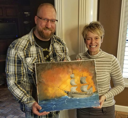"""Author Thomas Phillips is seen with Wichita Falls artist Jenny Kuehner Bechtold holding a painting of the She Wolf pirate ship that is featured on the cover of Phillips' debut novel """"Andalon Awakens."""""""