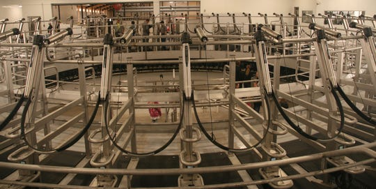 Operating in a clockwise rotation, the carousel brings cows right to the parlor operators who wipe the udders and attach the milking units.