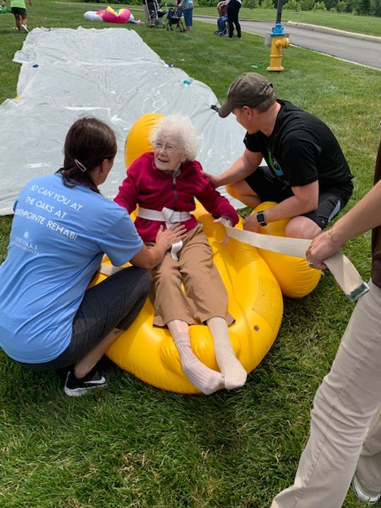 94-year-old Millie smiles after sliding down the slip 'n' slide at The Oaks at Northpointe.
