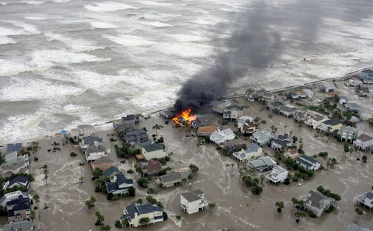 Fire destroys homes along the beach on Galveston Island, Texas as Hurricane Ike approaches on  Sept. 12, 2008.