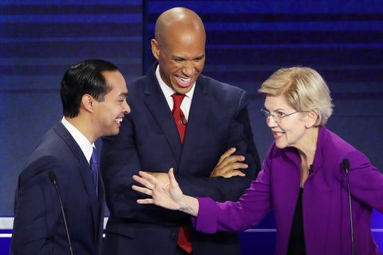 Former housing secretary Julian Castro, Sen. Cory Booker, D-N.J., and Sen. Elizabeth Warren, D-Mass., talk during the first night of the Democratic presidential debate in Miami on June 26, 2019.