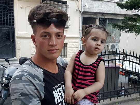 Feuzi Zabaat, 17, poses with toddler Doha Muhammed he caught as she was falling from the second floor at Fatih district in Istanbul on June 27, 2019.