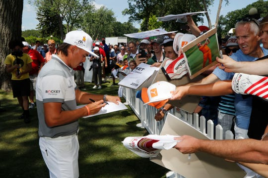 Rickie Fowler signs autographs during the Pro-Am for the Rocket Mortgage Classic.