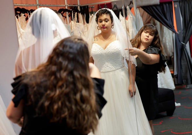 Ann Campeau, right, owner of Strut Bridal, fits a new dress on inventory manager Stefanie Zuniga at her shop in Tempe, Ariz.