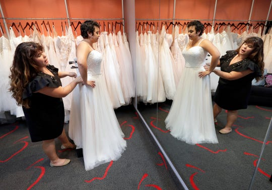 Ann Campeau, left, owner of Strut Bridal, fits a new dress on inventory manager Stefanie Zuniga at her shop in Tempe, Ariz.