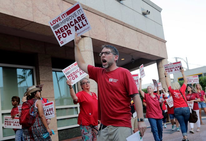 People with National Nurses United march in support of Medicare for All, outside the Knight Concert Hall at the Adrienne Arsht Center for the Performing Arts of Miami-Dade County, before a June 26, 2019, Democratic presidential debate.