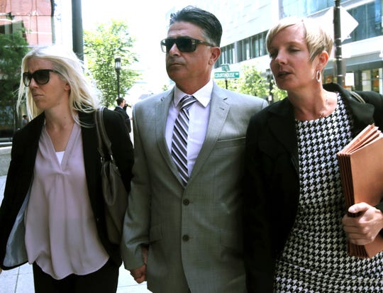 Former USC women's soccer coach Ali Khosroshahin, center, arrives at federal court Thursday, June 27, 2019, in Boston, where he is scheduled to plead guilty to charges in a nationwide college admissions bribery scandal.