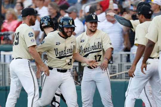 Vanderbilt designated hitter Ty Duvall celebrates with teammates after scoring a run during the fourth inning.