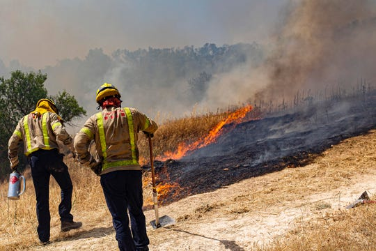 Firefighters try to extinguish a wildfire in Palma d'Ebre, near Tarragona, Spain, Thursday, June 27, 2019.