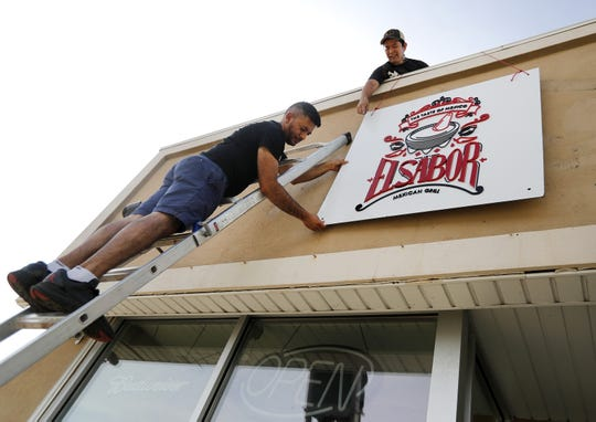 Alex Santiago, owner of El Sabor Mexican Grill, puts up his restaurant sign with help from Julio Vazquez.