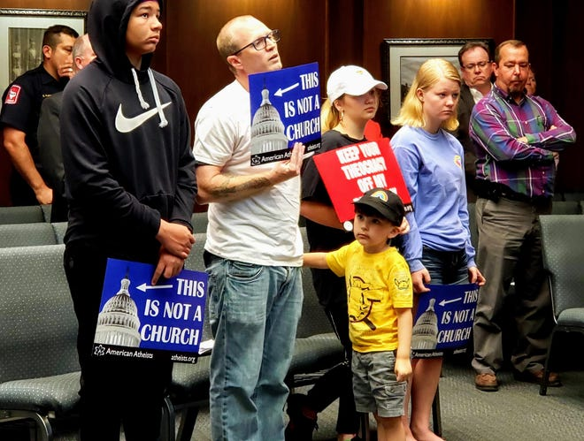 """A small group held up protest signs during the public prayer portion of Thursday night's Abilene City Council meeting. The group left shortly after, but Jeremy Wood (in white) later returned and addressed the council in public comments, saying he and others were frustrated that a previous request for the inclusion of a """"secular invocation"""" was denied."""