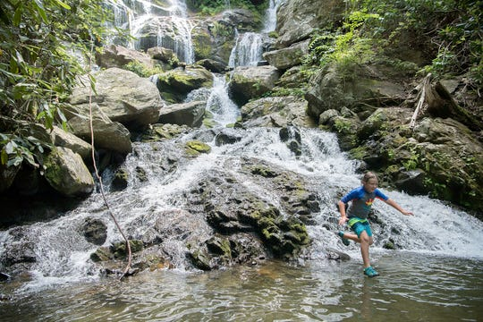 "Max Anthony, 8, of Morganton, does a small leap into shallow water at the base of Catawba Falls in the Pisgah National Forest in Old Fort on June 28, 2019. Anthony's mom, Kim, said she was impressed by the expansion of the parking lot at the trailhead. ""We had a spot close to the front and it was big, usually trailheads are small. And it had a bathroom,"" she said."