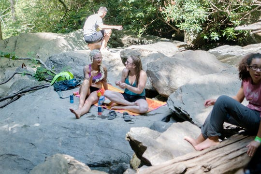 Anja Bartels, left, and Kelsey Sickmeyer, both of Asheville, enjoy snacks at the base of Catawba Falls in the Pisgah National Forest in Old Fort on June 28, 2019. Bartels said it is one of her favorite hikes because it is short if you only have a small amount of time to go hiking.