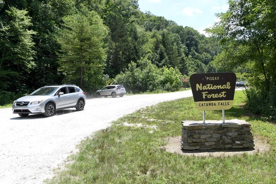 A vehicle leaves the parking area of Catawba Falls in the Pisgah National Forest in Old Fort on June 28, 2019. The parking lot was recently expanded to increase the amount of parking spots.