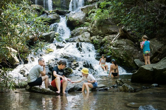 Brad Nowak, Teena McClelland and Evan Nowak, all of Chicago, look for special rocks in the water at the base of Catawba Falls in the Pisgah National Forest in Old Fort on June 28, 2019.