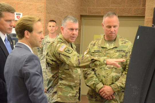 Sean Carlson, left, executive director of the Michigan Defense Center, and Lt. Governor Brian Calley are briefed in 2016 about the Fort Custer site by Brigadier General Michael Stone of the Michigan Department of Military Affairs and Lt. Col. Steve Wilson, commander of the Fort Custer Training Center