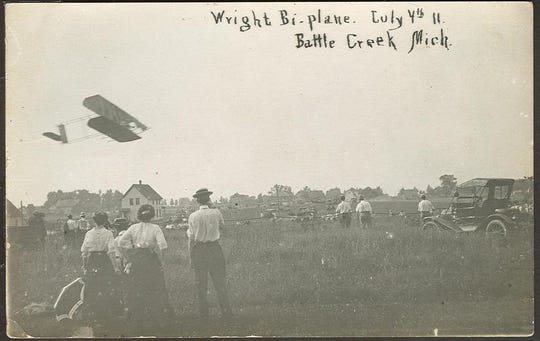 A Wright bi-plane, piloted by Leonard Bonney, flies over Athletic Field in Battle Creek on July 4, 1911. Bonney was the first to land a plane in Battle Creek when he visited as a member of the Wright Exhibition Team.