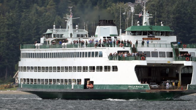 Riders aboard the Washington State Ferry Walla Walla line the rails as they watch a pod of orcas swim past in Rich Passage on Thursday, June 27, 2019.
