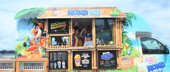 The Novick family smiles and waves from their Kona Ice truck.