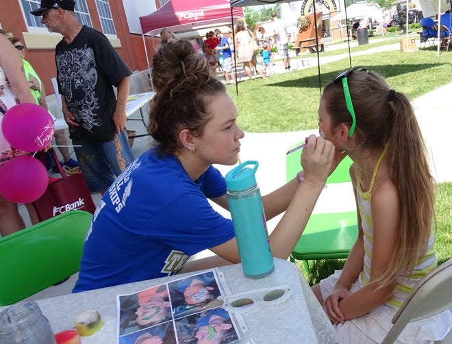 Katie Hopkins, who will be a senior at Colonel Crawford High School this fall, paints the face of Heaven Nelson, 10, at the Crawford County Arts Council tent during the ninth annual South of the Square Block Rally on Friday at Schines Art Park.
