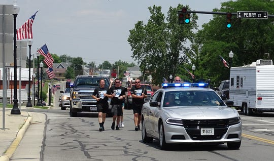 Bucyrus Police Officer Andrew Plummer carries the torch as the Ohio Special Olympics Law Enforcement Torch Run enters downtown Thursday on North Sandusky Avenue.
