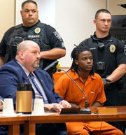 Terrance Matthews, suspect in three Willingboro murders, sits next to his public defender, John Keesler, at a court session in Mount Holly Friday.
