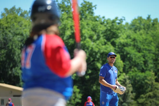 Iowa Cubs outfielder Jacob Hannemann helps children who are deaf or have partial hearing loss participate in the fifth edition of the Iowa Baseball Camp for the Deaf.