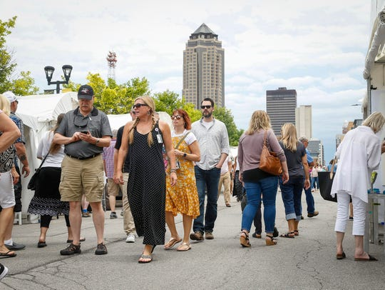 Art lovers mingle during the Des Moines Arts Festival in downtown Des Moines on Friday, June 29, 2019.