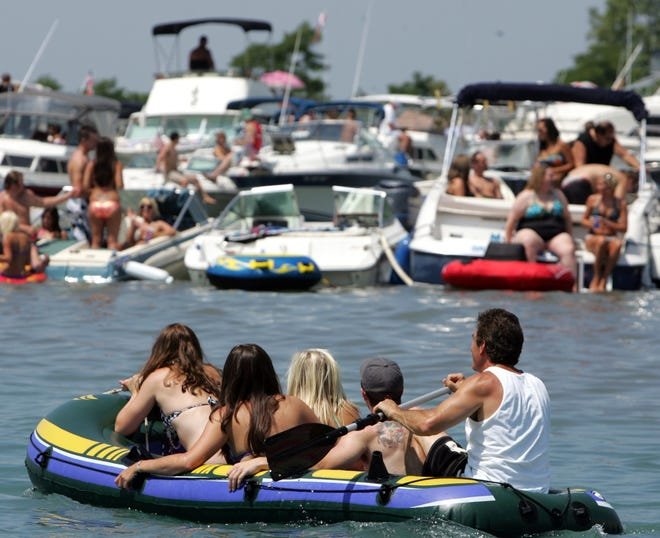 Boaters paddle their way through the water during Jobbie Nooner on Lake St. Clair off Harsens Island, Mich. on Friday, June 25, 2010.