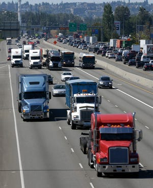 In this Wednesday, Aug. 24, 2016, file photo, truck and automobile traffic mix on Interstate 5, headed north through Fife, Wash., near the Port of Tacoma. Two U.S. senators have introduced a bill that would electronically limit tractor-trailer speeds to 65 miles per hour, a move they say would save lives on the nation's highways.