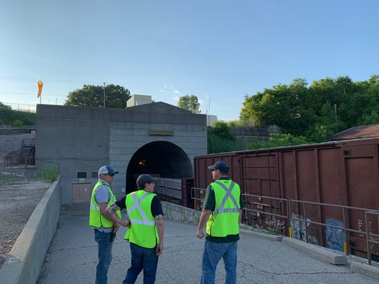 Workers discuss clean-up efforts in the Port Huron train tunnel.