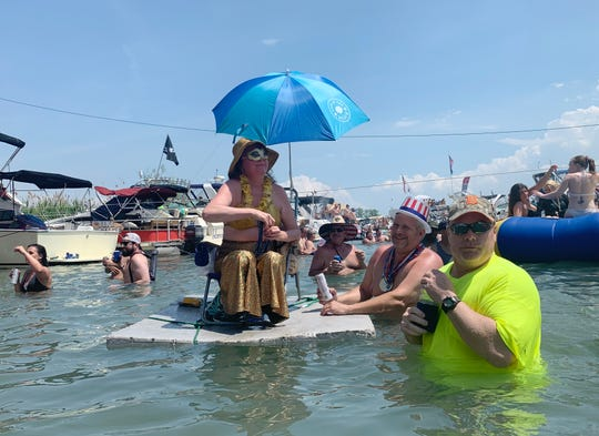 A Jobbie Nooner reveler dressed as a mermaid floats in the shallow water surrounding Gull Island.