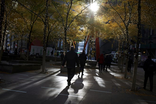 In this Nov. 14, 2018, file photo people walk through lower Manhattan's Zuccotti Park at the start of a work day in New York.