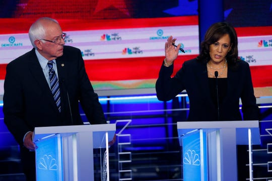 Democratic presidential candidate Sen. Kamala Harris, D-Calif., right, speaks , as Sen. Bernie Sanders, I-Vt., listens.